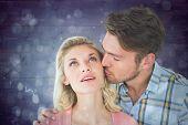 Handsome man kissing girlfriend on cheek against blue abstract light spot design