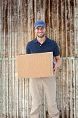 Happy delivery man holding cardboard box against wooden planks