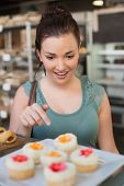Pretty brunette picking out a cupcake at the bakery