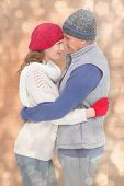 Happy couple in warm clothing hugging against light glowing dots design pattern