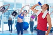 Composite image of fit man drinking water from bottle