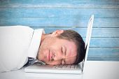 Tired businessman resting on laptop against wooden planks