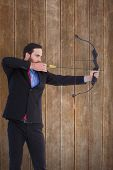 Focused businessman shooting a bow and arrow against wooden planks background