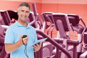 Trainer smiling at the camera against close up of treadmills in a fitness centre