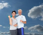 Happy fit couple with dumbbell and water bottle against sky and clouds
