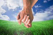 Happy senior couple holding hands against green field under blue sky