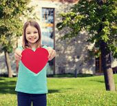 love, happiness and people concept - smiling little girl giving red heart