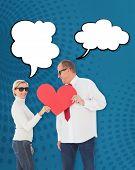 Older affectionate couple holding red heart shape against blue