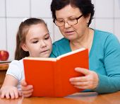 Grandmother Is Reading Book With Her Granddaughter