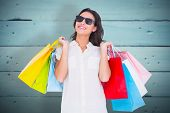 Pretty brunette with shopping bags against painted blue wooden planks