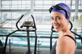 Fit swimmer standing by the pool smiling at camera against cross trainer machines overlooking large swimming pool
