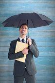 Businessman sheltering under umbrella holding file against wooden planks