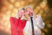 Silly couple holding hearts over their eyes against light circles on black background