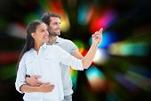Cute couple embracing and pointing against blurred lights