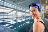 Fit swimmer standing by the pool smiling at camera against empty swimming pool with large windows