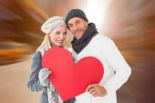 Smiling couple in winter fashion posing with heart shape against blurry new york street