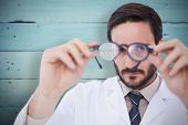 Doctor wearing lab coat looking through eyeglasses against painted blue wooden planks