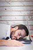 Businessman resting head on laptop keyboard against wooden planks