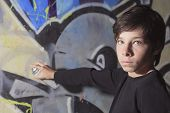 A teen made some graffiti on the wall of a tunnel