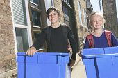 Two kids with a recycle bin outside