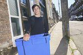 A teenager boy with recycle bin outside