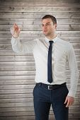 Young serious businessman pointing against wooden planks background