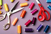 Multicolor sewing threads with scissors on wooden background