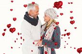Happy couple in winter fashion embracing against red heart balloons floating