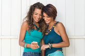 Portrait Of Two Smiling Young Women Looking At Cellphone In Summertime