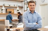Portrait of smiling young businessman with armcrossed looking at camera in office