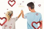 Young couple painting with roller against hearts