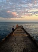 stock photo of paysage  - Little boy enjoying sea sunset on the pier - JPG