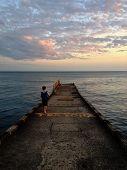 stock photo of paysage  - Little boy enjoying sea sunset on the pier - JPG