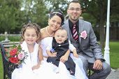 A newly wed couple and children with wedding gown, dark suit and