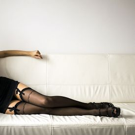 stock photo of legs apart  - Long sexy Woman legs in black stockings on sofa with high heels resting on sofa  - JPG