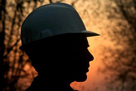 stock photo of labor  - Silhouette of a mining labor against strong back light - JPG