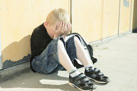 picture of school bullying  - A very sad boy who was bullied on a school playground - JPG