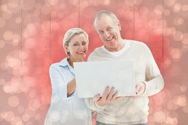 picture of male pattern baldness  - Happy mature couple using laptop against light glowing dots design pattern - JPG