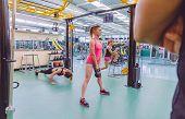 Постер, плакат: Trainer looking women group training in crossfit circuit