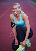 image of race track  - young runner sporty woman relaxing and stretching on athletic race track - JPG