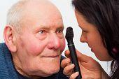 stock photo of cataract  - Optician checking elderly patient - JPG