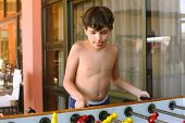 stock photo of preteen  - handsome preteen boy plays table soccer in beach recreation area - JPG