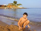 stock photo of preteen  - preteen handsome boy swimming on the red sea beach and yaht background - JPG