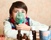 stock photo of inhalant  - boy with electric inhaler as a curation against virul disease flue