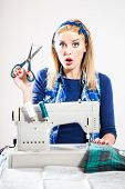stock photo of thread-making  - Woman sews and realizes that she is making mistake - JPG