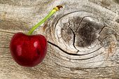 stock photo of black-cherry  - Close up of a single ripe large black cherry on rustic wood - JPG