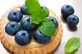image of curd  - Shortbread home made tartlet filled with lime curd and blueberries on old vintage metal background - JPG