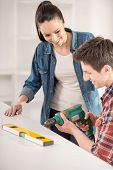 pic of hand drill  - Young man building furniture using hand drill at home - JPG