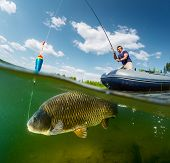 stock photo of fishermen  - Split shot of the fisherman with rod in the boat and underwater view of the big fish  - JPG