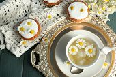 image of chamomile  - Cup of chamomile tea with chamomile flowers and tasty muffins on tray - JPG